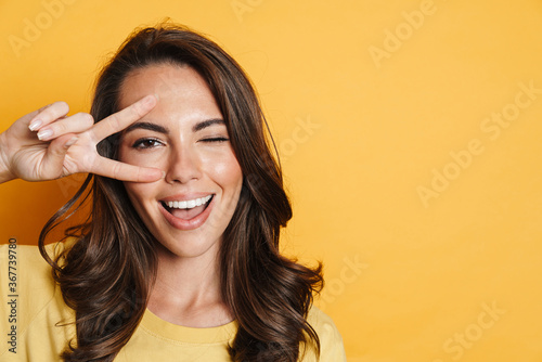 Valokuvatapetti Image of joyful brunette woman winking while gesturing peace sign