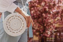 Close Up Of Bag In Fashionable Elegant Woman`s Outfit: Trendy White Wicker Small Shoulder Bag. Model Posing In Street With Blooming Tree, In European City. Copy, Empty Space For Text
