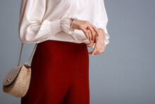 Close Up Of Fashionable Elegant Woman`s Outfit: Trendy Small  Shoulder Bag, Stylish Wrist Watch, Beautiful Ring With Red Gem. Model Posing On Blue Background. Copy, Empty Space For Text