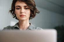 Image Of Young Focused Woman Working With Laptop While Sitting At Table