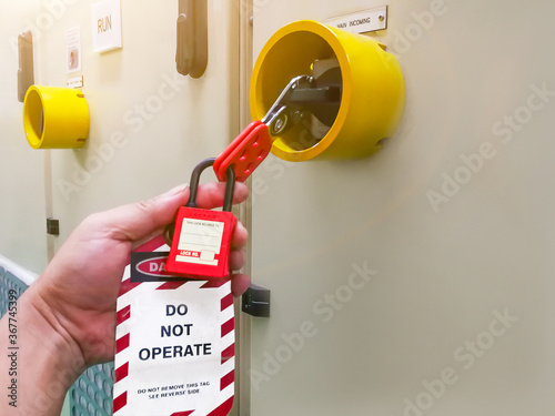 Obraz Hand holding red key lock and tag for process cut off electrical,the toggle tags number for electrical log out tag out - fototapety do salonu