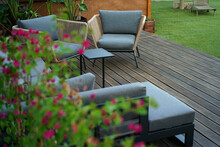 Beautiful Relaxing Spot In The Garden With Comfortable Chairs And Sofa Standing On A Wooden Deck Terrace Near The Green Grass