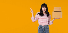 Happy Casual Asian Woman Carrying A Delivery Box That Has Been Packaged For Shipping. Ready To Point  Finger In The Blank Space Isolated On Bright Orange Background.