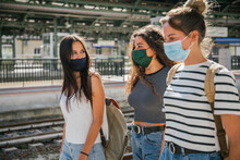 Three Young Friends Women At The Station Waiting Train For Their Trip In Summer With Face Mask For Protection By Infection From Corona Virus, Covid-19 - Millennials Having Fun Together