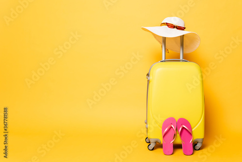 Fototapeta yellow travel bag with flip flops, sun hat and sunglasses isolated on yellow obraz