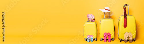 family travel bags with beach summer accessories isolated on yellow, panoramic shot - 367781765