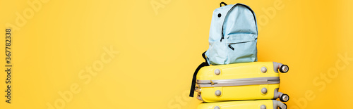 blue backpack on travel bags isolated on yellow, panoramic shot