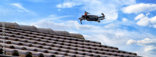 Obraz Drone in the air inspecting the roof over the house. Close-up of drone and roof. - fototapety do salonu
