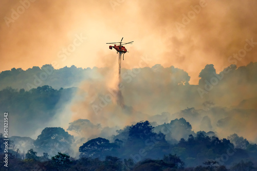 Photographie Firefithing helicopter dropping water on forest fire
