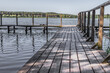 Wooden pier on the lake. Rural landscape. Place of power. The beauty of the countryside. Pacification of nature. An ideal place for meditation. Boardwalk pier for fishing.