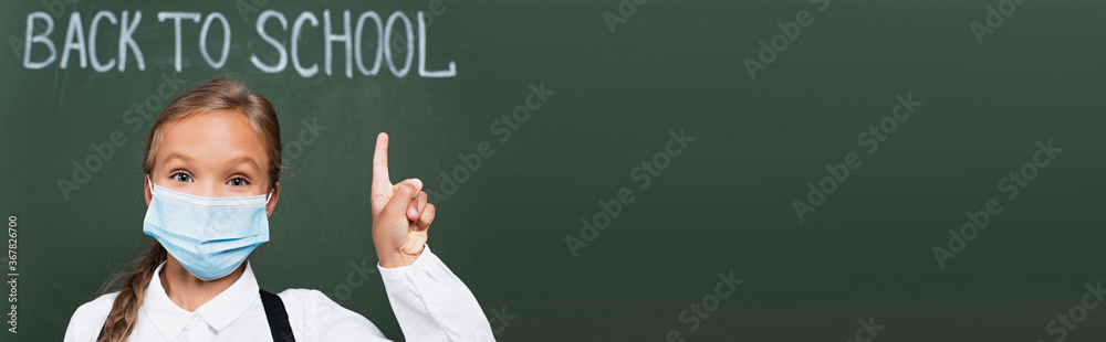 Fototapeta horizontal image of schoolgirl in medical mask pointing with finger near chalkboard with back to school inscription