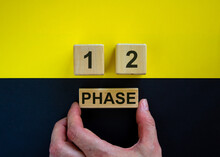 Businessman Holds A Block With Word 'phase'. Wooden Cubes With Numbers 1 And 2. Beautiful Yellow And Black Background. Copy Space. Concept Of Choice.