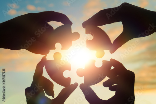 Obraz Four hands of businessmen put together a puzzle against the backdrop of a dramatic sky at sunset. Business concept idea, collaboration, teamwork, partnership, innovation - fototapety do salonu