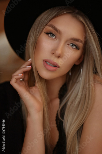 Fashion portrait of a model girl with gentle makeup and platinum blond straight hair wearing black trendy hat
