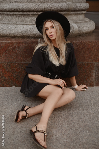 A young woman with blond hair in a trendy hat and black dress posing outdoors at the city