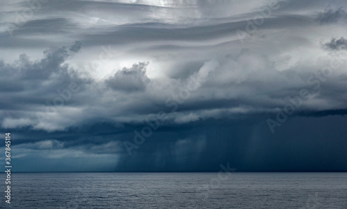 Fototapeta Heavy rainy clouds pouring rain over the ocean