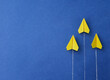 Yellow paper planes on a blue background. The concept of moving towards success. Upward movement.