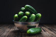 Freshly Picked Juicy Cucumbers In A Metal Colander On A Brown Wooden Table