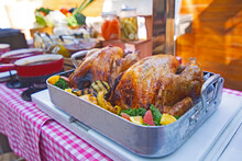 Roasted Turkey Garnished With Potato, Vegetables, And Cranberries On A Rustic Style Table. Christmas Dinner BBQ.