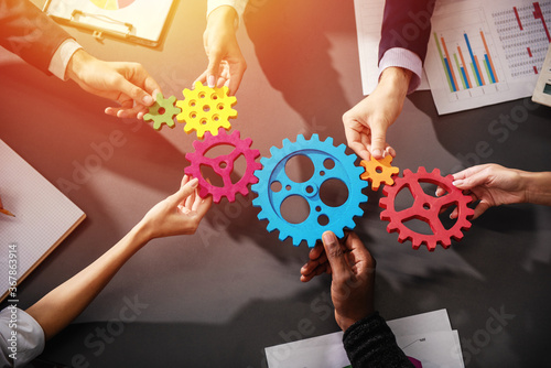 Business team connect pieces of gears. Teamwork, partnership and integration concept - 367863914