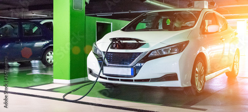 Obraz Eco auto. Electric car charge battery on eco energy charger station. Hybrid vehicle - green technology of future. Clean energy future of transportation ecology concept. - fototapety do salonu