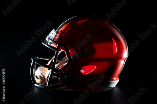 Obraz Professional gear and competitive sports concept with dramatic low key photograph of American football helmet with face mask in the dark isolated on black background with clipping path cutout - fototapety do salonu