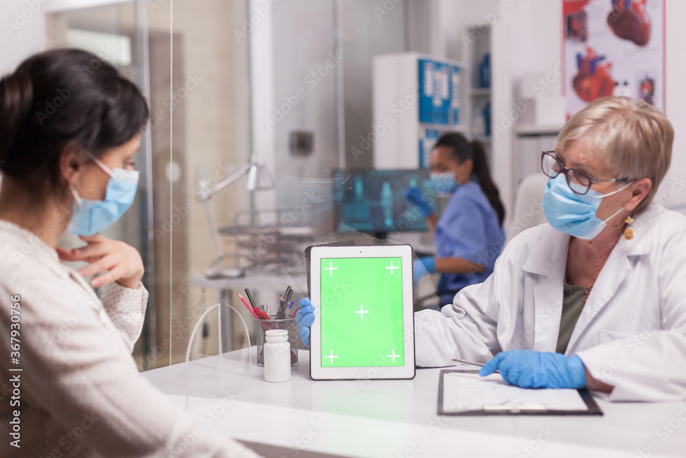 Fototapeta Doctor with face mask looking at tablet with green screen during consultation with sick patient. Nurse wearing blue uniform.