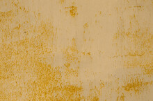 Texture Of Rusty Corrosive Metal Fence, With Flattened Yellow Paint From Dilapidation. Rusty Non Ferrous Metal. Cracks Of Yellow Paint From Weathering On The Surface Of The Metal Sheet..