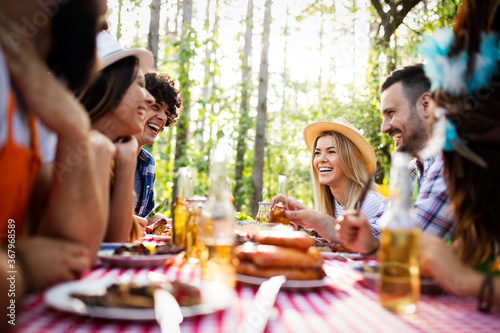 Group of happy friends eating and toasting at garden barbecue