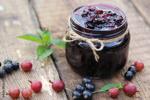 Obraz Berry jam in a jar. Preservations. Black currant and gooseberry jam, fresh mint and chamomile on an old wooden table. Rustic. Background image, copy space, horizontal - fototapety do salonu