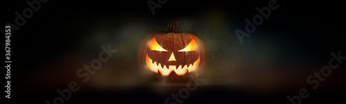 One spooky evil halloween lantern, Jack O Lantern, with glowing eyes and face on a dark background Canvas