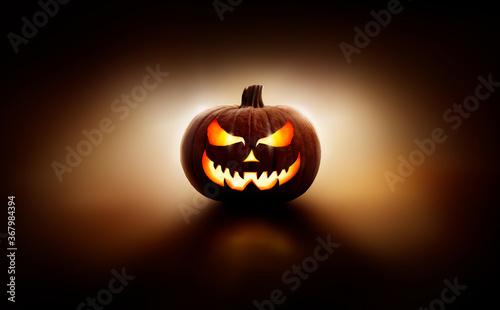 Obraz A back lit halloween lantern, Jack o Lantern, with a spooky evil face with glowing eyes against a dark background. - fototapety do salonu