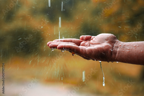 Leinwand Poster rain water falling on hand
