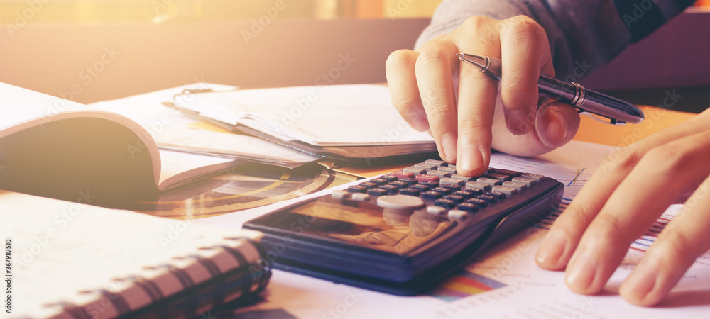 Fototapeta Woman using calculator with doing finance at home office.