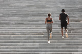 Fototapeta Na drzwi - Outdoor sport. Black couple running on stairs in city park, rear view