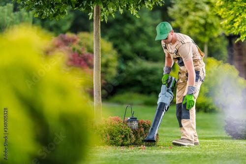 Obraz Gardener with Cordless Leaf Blower Cleaning Backyard Garden - fototapety do salonu