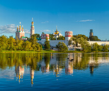 The Famous Moscow Landmark With Golden Domes And A Reflection Of The Landscape On The Water Of The Park Pond Against The Background Of A Picturesque Blue Sky With Clouds.