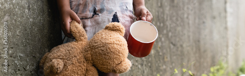 Foto Panoramic crop of beggar african american child holding teddy bear while begging