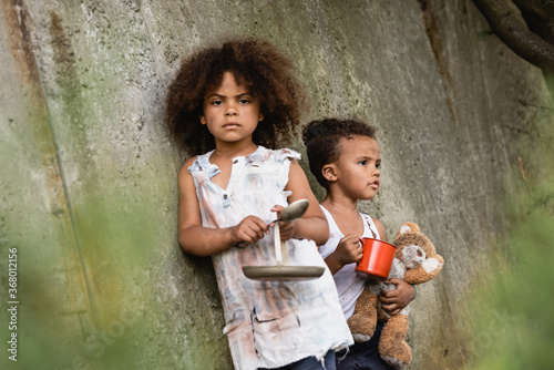 Selective focus of poor afrian american kid holding metal spoon and plate near b Canvas