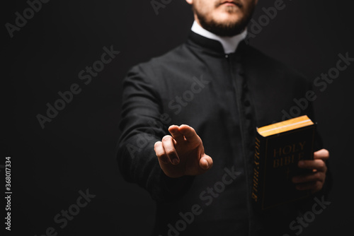 Fototapeta selective focus of priest holding holy bible while gesturing isolated on black