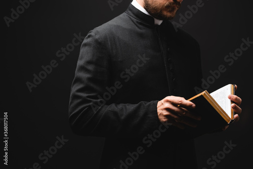 Fotografia partial view of bearded priest holding holy bible in hands isolated on black