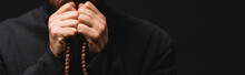 Panoramic Crop Of Priest Holding Rosary Beads In Hands Isolated On Black