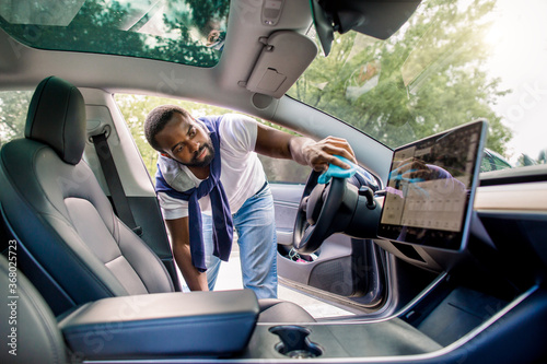 Obraz Cleaning service, car detailing concept. Young dark skinned man in t-shirt and jeans, washing a car interior, car steering wheel with microfiber clothes, in his modern futuristic high tech car - fototapety do salonu
