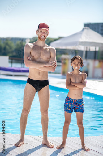 Man and boy in swimming suits near pool