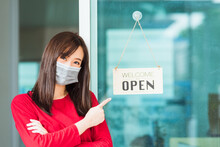"""New Normal Asian Young Woman Wear Face Mask Protect Glad Point Finger To Notice Sign Wood Board Label """"WELCOME OPEN"""" Hang Through Glass Door Front Shop, Business Turn Open After Coronavirus Pandemic"""