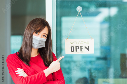 Fotografija New normal Asian young woman wear face mask protect glad point finger to notice