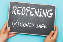 Hands Holding Chalkboard With Notice Reopening Covid Safe