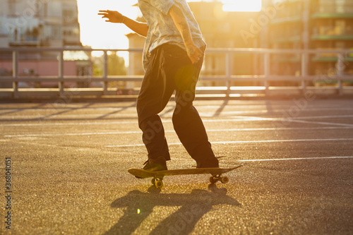 Skateboarder doing a trick at the city's street in summer's sunshine. Young man in sneakers and cap riding and skateboarding on the asphalt. Concept of leisure activity, sport, extreme, hobby and