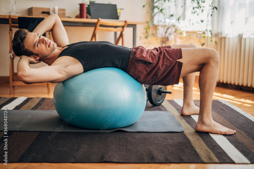 Fototapeta Young man doing doing sit ups on exercise ball at home