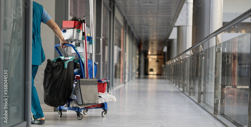 An employee pulls a trolley for cleaning offices Fototapeta